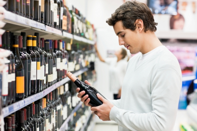 Man Looking at Bottle of Wine